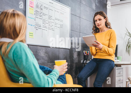 Deux business woman having meeting devant le tableau blanc Banque D'Images