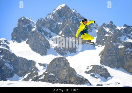 Un homme passe en skis dans la station alpine de Courchevel, avec le sommet de la Saulire en arrière-plan. Banque D'Images
