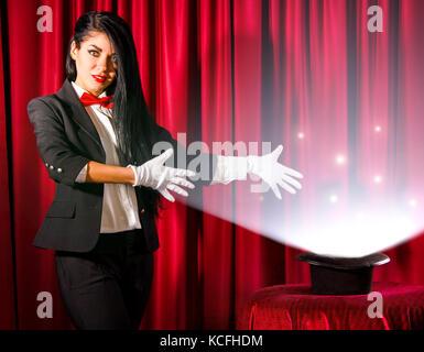 Belle jeune magicien montrant à un chapeau avec les lumières et les fumées de sortir