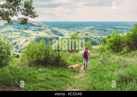 Fille et son chien à marcher le long d'un sentier de randonnée Banque D'Images