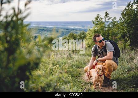 L'homme portant des lunettes de soleil avec un petit chien jaune se reposant à la sentier de randonnée pédestre Banque D'Images