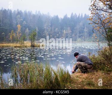 Lave-randonneur son visage au matin d'automne dans le parc national, la Finlande Banque D'Images