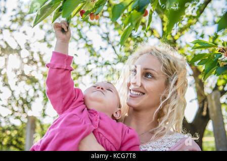 Mère avec bébé la cueillette et Eating in Garden Banque D'Images