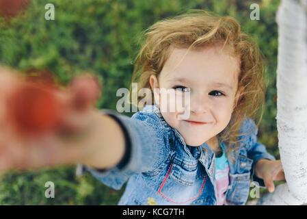 Happy little girl cherry picking in garden Banque D'Images