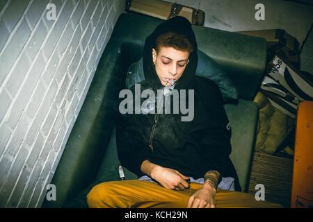 Jeune homme toxicomanes consommant des drogues illégales en position couchée sur t Banque D'Images