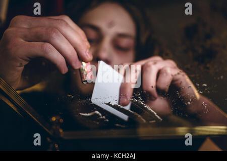 Gros plan des mains d'un jeune homme toxicomane en poudre par voie nasale Banque D'Images