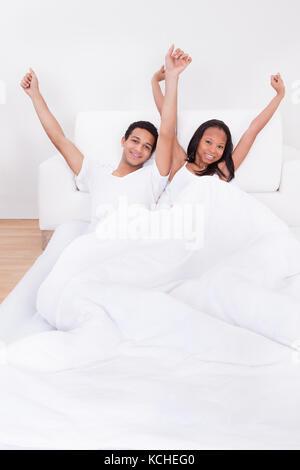 Portrait of happy couple sensibilisation mains on bed Banque D'Images