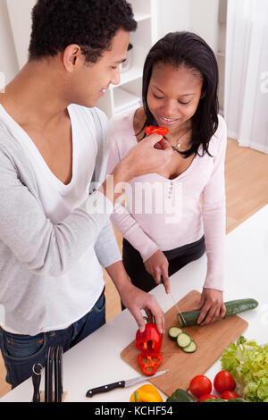 Portrait of couple chopping vegetables in kitchen Banque D'Images
