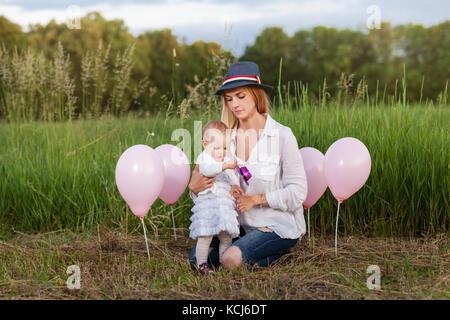 Mère et fille assis dans un pré entre les ballons roses Banque D'Images
