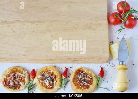 Fond rustique blanc avec planche à découper en bois, de biscuit dans une forme de pizza avec du chili, romarin, Banque D'Images