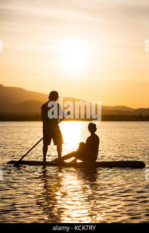 Un jeune couple en silhouette, pagaies un stand up paddle board comme soirée ensembles dans alors qu'à la fin du Banque D'Images