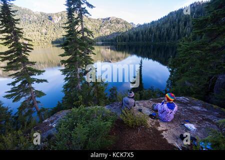 Deux amies, campant au lac Bedwell, dégustez un café tôt le matin. Strathcona Park, Central Vancouver Island, Colombie Banque D'Images