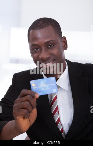 Portrait of happy young woman holding credit card Banque D'Images