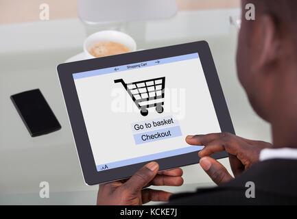 African businessman holding digital tablet avec des achats en ligne sur un écran d'application Banque D'Images