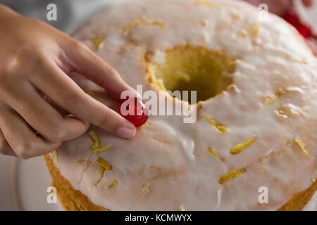 Close-up of woman toping un gâteau fraîchement cuit au four avec Cherry Banque D'Images