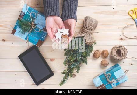 Vue de dessus de woman's hands holding coockies maison pour Noël dans un style rustique Banque D'Images