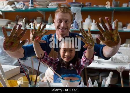 Potter mâles et une fille montrant leurs mains peintes en atelier de poterie Banque D'Images