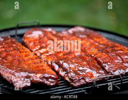 La cuisson des côtes de porc barbecue sur un fumeur Banque D'Images