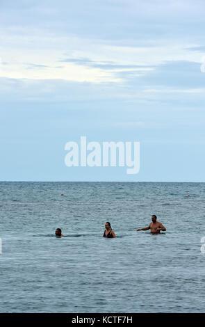 Trois personnes wild nager dans la mer au large de la côte de Corfou en Grèce lors d'une journée ensoleillée dans Banque D'Images