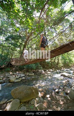 Les touristes marcher sur un pont suspendu à travers rio colorado dans Rincon de la Vieja Volcano National Park Banque D'Images