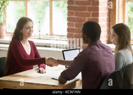 Smiling woman shaking hands with african american représentant RH ou nouveau collaborateur. employés saluent avant; Banque D'Images