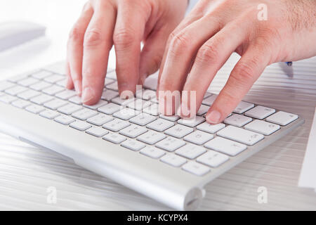 Close-up of male hands typing on computer keyboard Banque D'Images