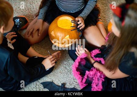 Voir ci-dessus de trois enfants vêtus de costumes de Halloween à jouer à Magic Lantern citrouille avec rituel sitting Banque D'Images