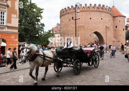 Une calèche passe devant la barbacane, la vieille ville de Varsovie, Pologne.