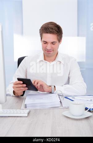 Happy young woman calcul de factures à 24 Banque D'Images