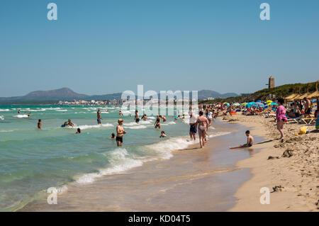 Les touristes à la plage de Playa de Muro à Can Picafort ville et montagnes en arrière-plan, la partie nord de l'île Banque D'Images
