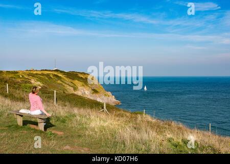 Dame prend un reste de marcher le south west coast path à Berry Head, Brixham, Devon regardant la mer à une seule Banque D'Images