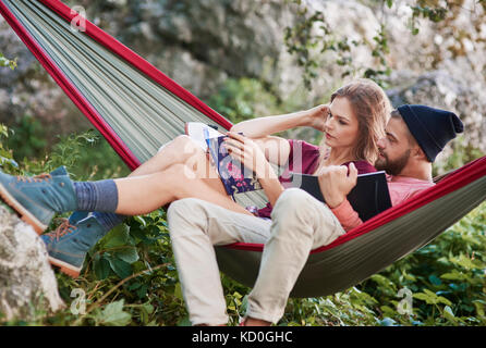 Couple relaxing in hammock reading books, Cracovie, Pologne, europe, malopolskie Banque D'Images
