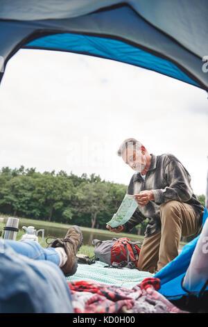 Mature Woman relaxing in tent, l'homme à l'extérieur tente, looking at map Banque D'Images