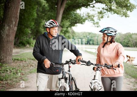 D'âge mûr à marcher le long des sentiers ruraux bicyclettes Banque D'Images