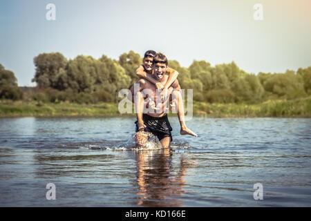 Les enfants espiègles s'amusant sur river lors des vacances en campagne symbolisant l'enfance insouciante Banque D'Images