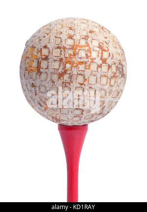 Old golf ball on a tee rouge isolé sur fond blanc.