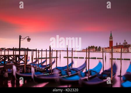 Lever de soleil sur spectaculaire Venise, Italie. au premier plan sont l'emblématique et gondoles sur le canal est l'île de San Giorgio Maggiore.