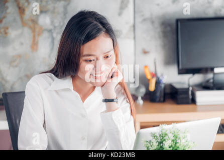Asian businesswoman looking at laptop computer et visage souriant et de repos avec des professionnels de l'émotion Banque D'Images