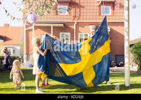Père avec ses filles (18-23 mois, 8-9) holding drapeau suédois Banque D'Images