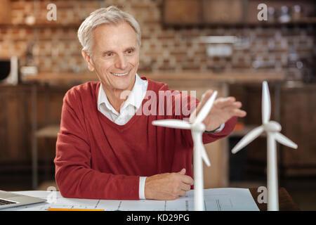 Man joyeux atteignant une main vers les modèles d'éolienne Banque D'Images
