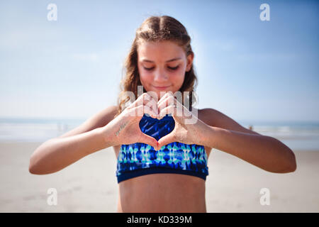 Girl making heart shape with hands on beach Banque D'Images