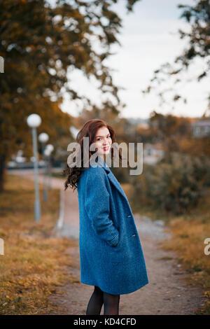 ... Jeune femme à la mode bouclés à l automne dans le parc de sourire et 9a780ce0be8