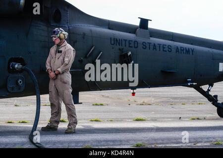 U.s. marine cpl Jason d. moxley, affecté à la 273e Escadron de soutien de l'aile marine, air operations company, attend comme un UH-60 Blackhawk est alimentée pendant les opérations de ravitaillement en vol à mcentire point la base de la garde nationale conjointe, L.C. (le 14 mai 2014. éléments de la Caroline du Sud et de l'armée de l'air national guard et l'us marines mener des opérations conjointes qui sont essentiels au succès continu de la préparation opérationnelle et des déploiements à travers le monde. La garde nationale américaine (photo par le sgt tech. Jorge intriago/libérés)