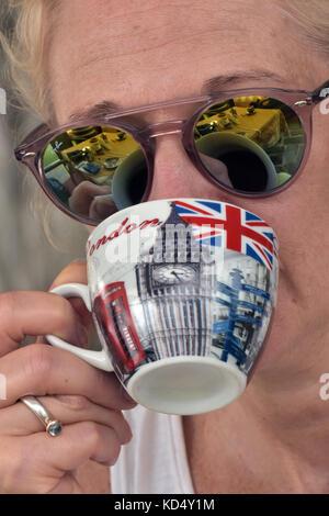 Une femme à boire le thé dans une tasse peinte en rouge, blanc et bleu avec des photos de Big Ben, un téléphone Banque D'Images