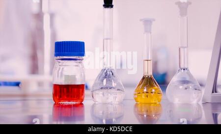 Flacons de laboratoire et gobelets avec des liquides de différentes couleurs sur table lab Banque D'Images