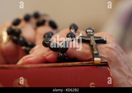 Une vieille femme priant le Chapelet sur le dessus de sa bible Banque D'Images