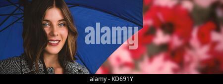 Portrait de femme avec parapluie bleu contre les feuilles d'érable tombé sur route Banque D'Images