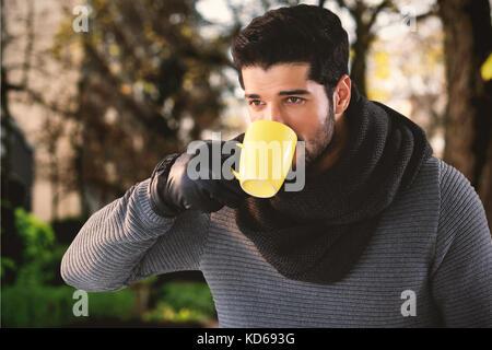 Young man having coffee contre sentier d'arbres en ville Banque D'Images