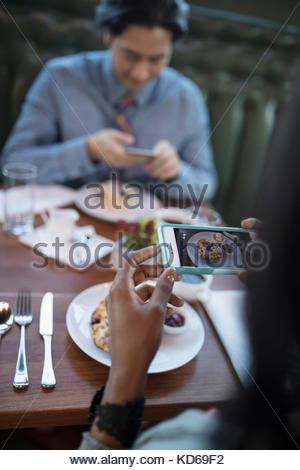 Couple avec les téléphones avec appareil photo photographier food, restaurants au restaurant table Banque D'Images