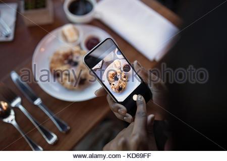 Point de vue personnel femme avec téléphone appareil photo photographier food, restaurants au restaurant table Banque D'Images